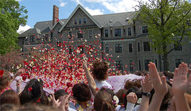 Photo of jubilant crowd tossing flower petals into the air