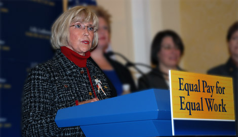 "photo of Lilly Ledbetter at a podium labeled ""Equal Pay for Equal Work"""